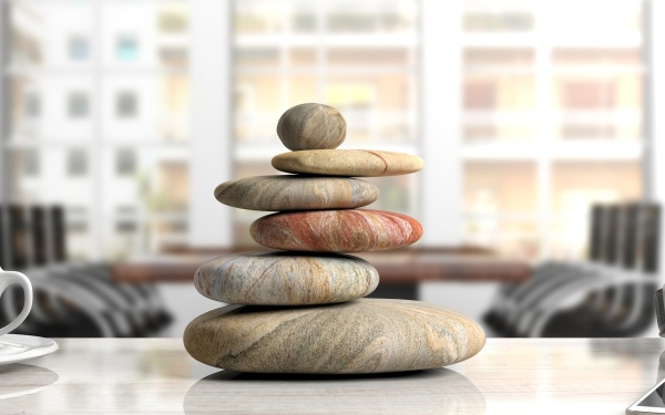 Relaxation at the office. Zen stones stack on an office desk. 3d illustration